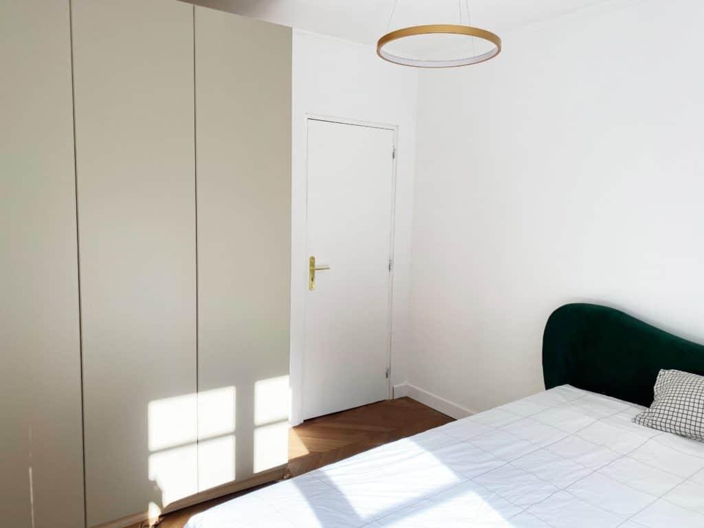 Chambre aménagée lit velours vert parquet chevron suspension led