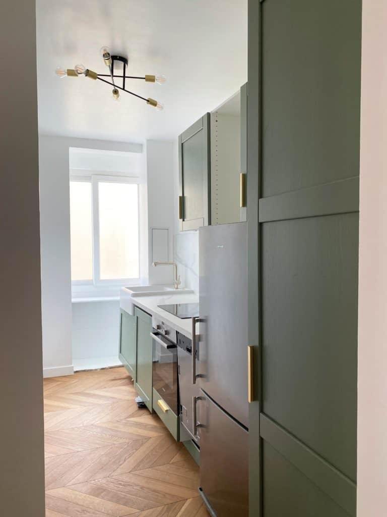 Cuisine rénovée parquet chevron meubles verts plafonnier doré et noir