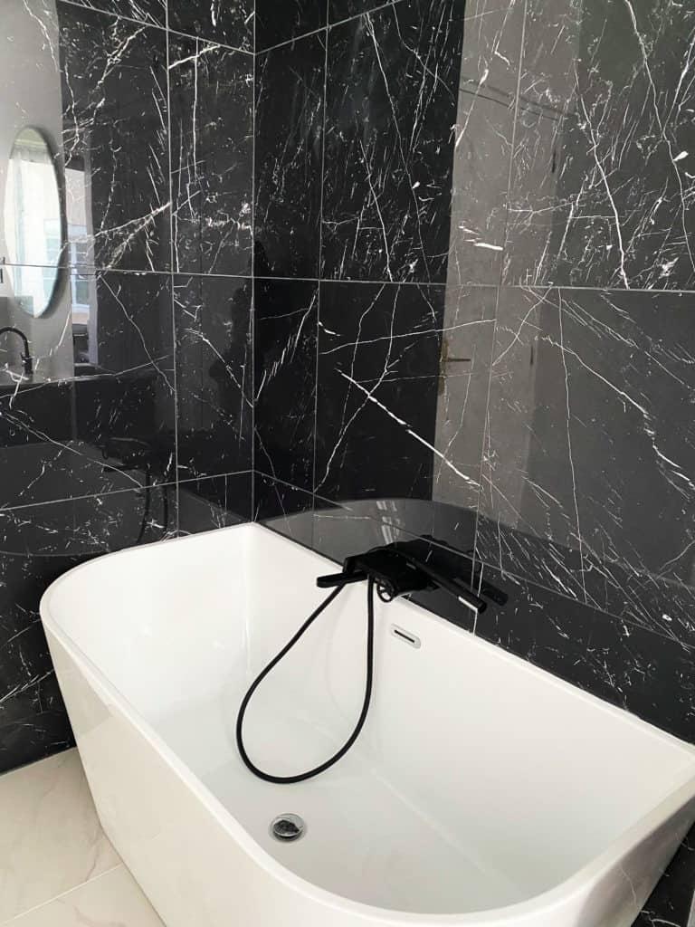 Baignoire semi-ilot blanche acrylique salle de bain marbre noir mur