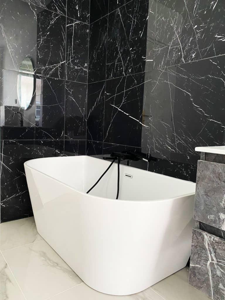 Rénovation salle de bain baignoire semi-ilot blanche bains design carrelage marbre noir