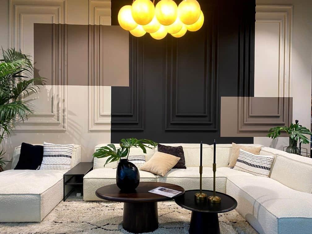 Salon luxe moulures murales canapé d'angle bouclette blanc tables basses noires