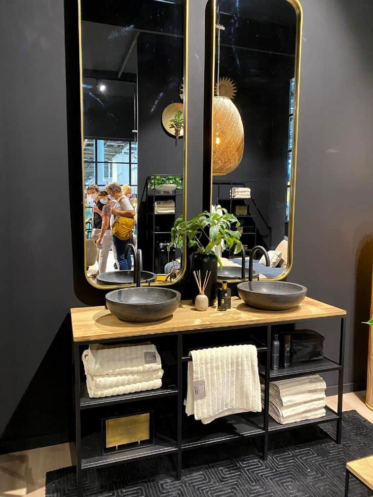 Salle de bain murs noirs double vasque béton robinet noir miroir doré allongé