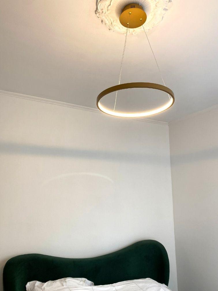 Suspension LED circle dorée dessus lit velours vert